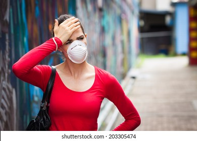 A woman with headache wearing a face mask in the city