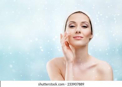 Frau mit einem Headband, das Gesichtspflegeverfahren in der Winterzeit, Schneefall-Hintergrund