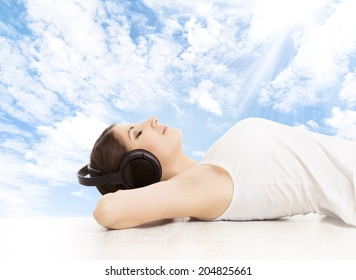 Woman in headphones dreaming listening to music. Girl relaxing over blue sky background