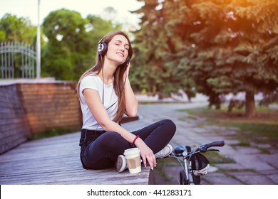 Woman in the headphones drinking coffee. Beautiful girl relaxing and listen music in the city park on blurred background.