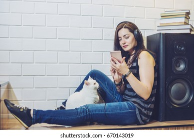 Woman in headphones listening to an audiobook on a phone sitting with cat on wall background. Concept of technology education