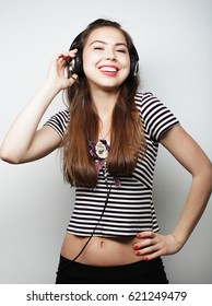 Woman with headphones listening music. Music girl dancing agains