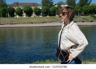 Woman in headphones listening to music on the street