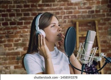 Woman in headphones recording music video blog home lesson, singing or making broadcast internet tutorial while sitting in loft workplace or at home. Concept of hobby, music, art and creation.