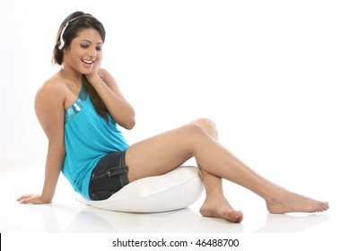 woman with headphones relaxing with pillow