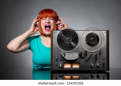 Woman in headphones with a retro reel audio tape recorder on dark background