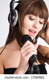 Woman in headphones Singing in to Microphone