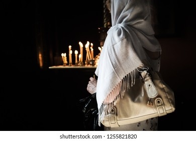 A woman in a headscarf holding prayer candles. In a Russian Orthodox church in Tallinn, Estonia.