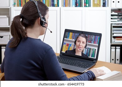 Woman with headset and book at her desk in front of her laptop having an online chat with her lawyer, text space