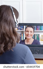 Woman with headset at her desk in front of her laptop making a video call with her friend, copy or text space