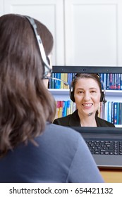 Woman with headset at her desk in front of her computer making a video call with her legal adviser, copy or text space