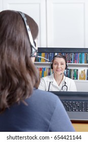 Woman with headset and laptop making a video call with her doctor, copy or text space, e-health, telehealth or telemedicine concept