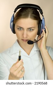 Woman with headset and microphone discovering she´s unplugged