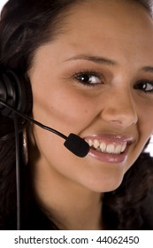 A woman with a headset with a smile on her face talking.