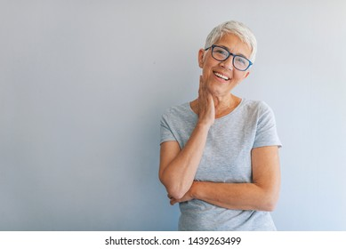 Woman headshot looking at camera. Portrait of beautiful mature woman. Portrait of businesswoman on grey background. Smiling senior woman.