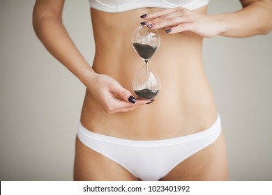 Woman Health Problem. Closeup Of Female With Fit Slim Body In Panties Holding Sand Clock Face Near Her Stomach. Digestive Disorders, Period Pain, Health Issues Concept. High Resolution