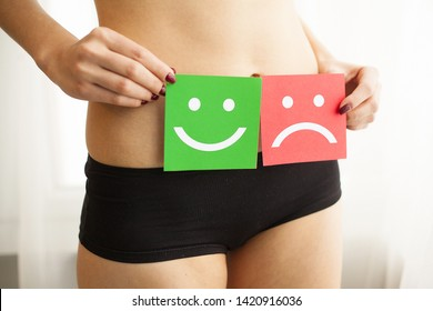 Woman Health Problem. Closeup Of Female With Fit Slim Body In Panties Holding Two Card With Sad Smiley And Happy Face Near Her Stomach. Digestive Disorders, Period Pain, Health Issues Concept