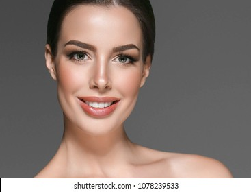 Woman with healthy beauty skin and teeth close up face portrait. Brunette long hair female young beautiful model skincsre photo. Studio shot.