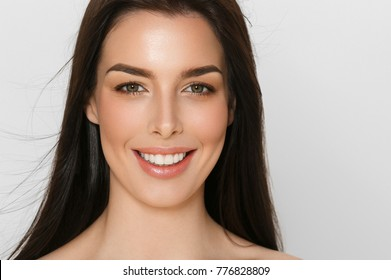Woman with healthy beauty skin and teeth close up face portrait. Brunette long hair female young beautiful model skincsre photo