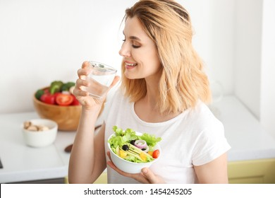 Woman with healthy vegetable salad and glass of water in kitchen