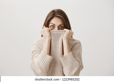 Woman hears terrifying story making her tremble from fear. Portrait of cute adult caucasian girl hiding in sweater, peeking out of collar with popped eyes being scared or shocked over gray wall