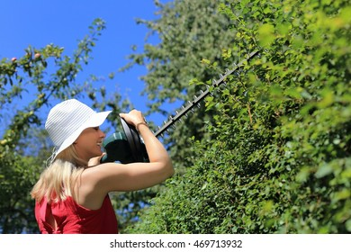 A Woman hedge cutting with summer hat