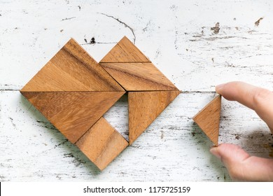Woman held piece of tangram puzzle to fulfill the heart shape on old white wood background (Concept of love)