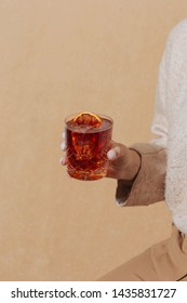 Woman helding Negroni, an italian cocktail, an apéritif, first mixed in Firenze, Italy, in 1919. Count Camillo Negroni asked to strengthen his Americano by adding gin rather than normal soda water.