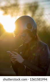 woman with helmet of motorcycle talking with mobile phone at the sunset