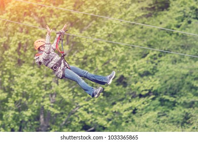 Woman in helmet is riding on a cable car in the mountains, sunny