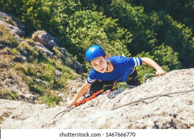 Woman in helmet and special equipment climbing high mountain via ferrata and looks at camera man. Crimea.