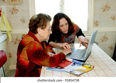 Woman helping grandmother with computer