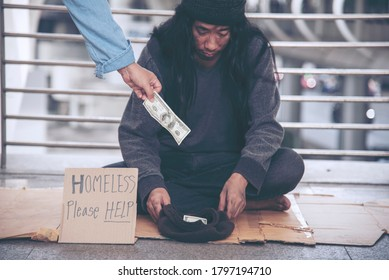 Woman helping hands to homeless people poverty beggar man holding hands asking for money job and hoping help in helpless dirty city sitting on streets. Desperate Beggar in city concept.