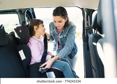 Woman helping her daughter to fasten seatbelts in the car, the girl is sitting on a safety child car seat