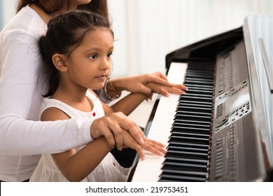 Woman helping her daughter to play the piano, body and buttons of the piano were digitally modified