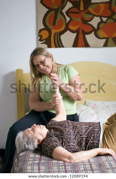 Woman helping her elderly mother with stretching and physical therapy exercises