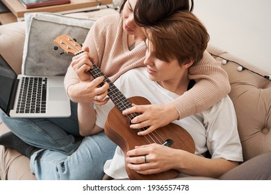 Woman helping her girlfriend to playing at the ukulele