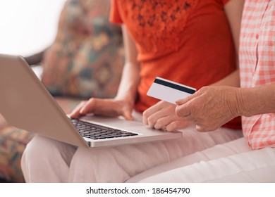 Woman helping her grandmother to make purchases on the internet
