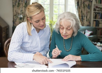 Woman Helping Senior Neighbor With Paperwork
