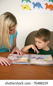 A woman helping a young child read a book