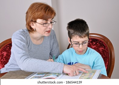 Woman helping young schoolboy to do his homework