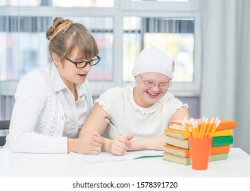 Woman helps young girl with Down Syndrome with homework at home