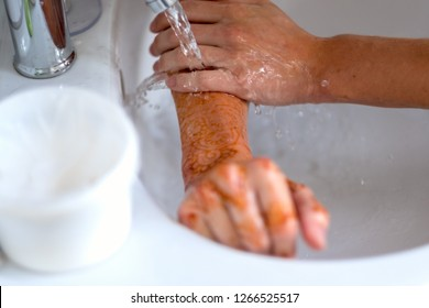 Woman with henna tattoo washing her hands under running water in a wash basin in a close up cropped view