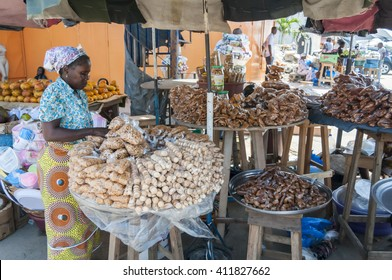 A woman in her 40s in a traditional African dress selling local Ivorian sweets and nuts at the Abidjan market. Abidjan, Ivory Coast, Africa, Circa May 2013. Benin, Togo, Zambia, Gambia, Guinea, Mali