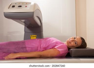 Woman in her 40s undergoing scan at bone densitometer machine.