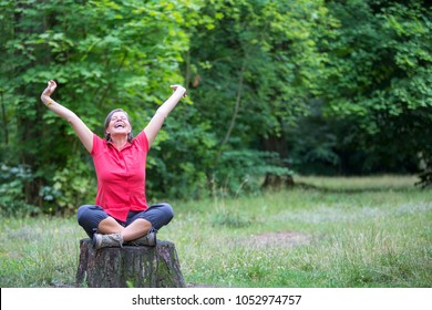 woman in her 50s sitting on a tree stump and is happy