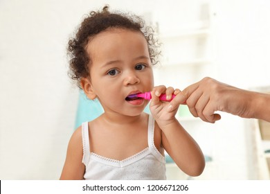 Woman and her African-American daughter with toothbrush on blurred background