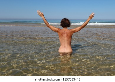 a woman with her arms in the air sitting in the water of the sea seen from behind and naked