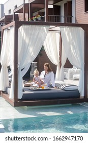 Woman and her baby girl are enjoying breakfast in outdoor daybed with side curtains next to the swimming pool, the perfect beginning of summer day