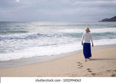 Woman with her back to the camera posing on the sea. Girl is walking on beach during a storm.